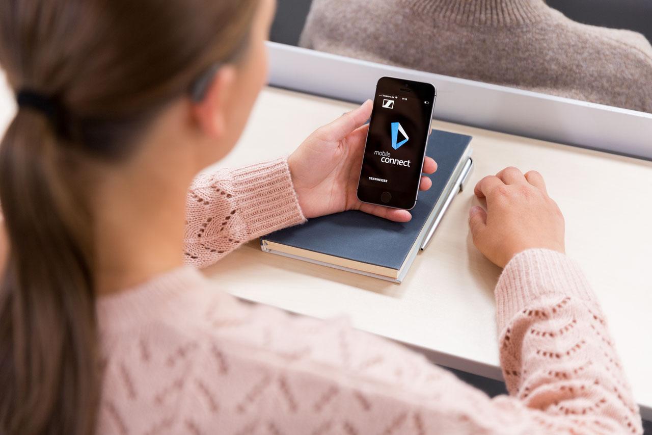 Sennheiser Mobile Connect Frau mit Handyapp in Hörsaal